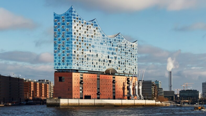 Fotografie der Elbphilharmonie in Hamburg aus Sicht von der Anlegerbrücke am Hafen.