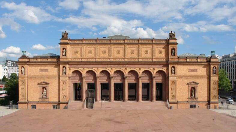Bild eines Gebäudes in hellem Ton in der Frontalansicht.