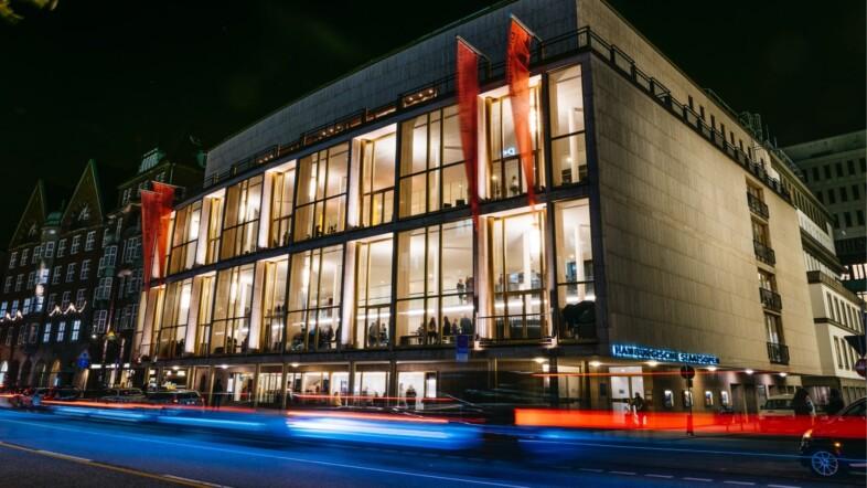 Außenansicht der Staatsoper Hamburg bei Nacht. Das Gebäude wir von außen mit blauen und roten Lichtern beleuchtet.