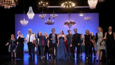 Gruppe von Schauspielern auf der Bühne. Von der Decke hängen Kronleuchter