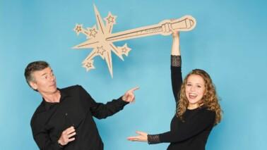Bild mit zwei Personen vor blauem Hintergrund und einem Zauberstab in der Hand.