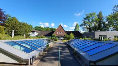 Außenansicht des Nordkolleg Rendsburg am Tage. Zu sehen ist ein Gang, der zu einem Haus führt. Links und rechts sind Solarplatten zu sehen. Der Himmel ist blau und die Sonne scheint.