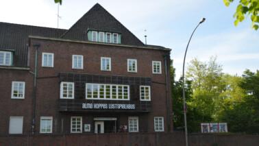 Fotografie eines Hauses in Backsteinarchitektur mit dem Schriftzug Alma Hoppes Lustspielhaus.