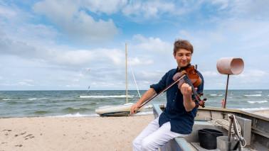 Ein Mann sitzt am Stand auf einem Boot und spielt Geige.