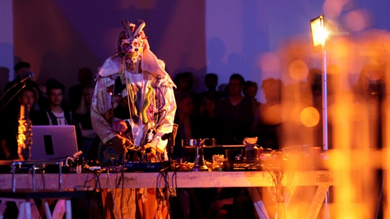 Fotografie eines Mannes in Kostüm an einem DJ Pult in lila orangener Beleuchtung.
