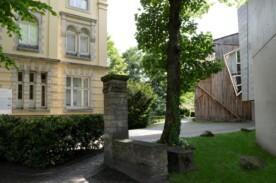 Gehweg mit einem Baum auf der rechten Seite und einem Gebäude im Hintergrund