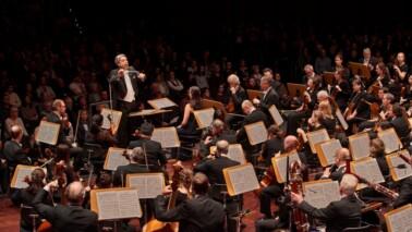 Fotografie eines Orchesters mit Blick zum Publikum. Die Augen der Musiker sind auf den Dirigenten gerichtet.