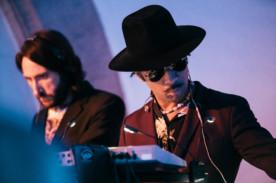 Foto von zwei Männern auf der Bühne, die jeweils ein Instrument spielen. Der Mann auf der rechten Seite trägt einen Hut, eine Sonnenbrille und einen Anzug. Der Mann auf der rechten Seite trägt ebenfalls einen Anzug und hat längeres, dunkles Haar.