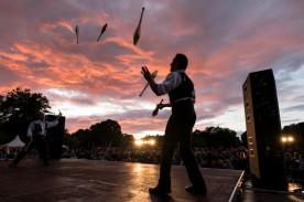 Foto eines Mannes, der auf der Bühne steht und jongliert. Die Sonne geht gerade unter und das Publikum ist im Hintergrund zu sehen.