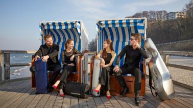 Vier Personen sitzen in Strandkörben am Strand und unterhalten sich.