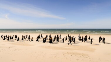 Fotografie eines Strandes, an dem mehere schwar gekleidete Personen entlang laufen.