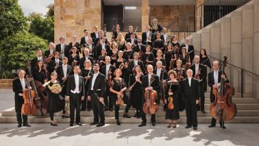 Mehrere Musiker*innen stehen schwarz/weiß gekleidet auf einer Treppe. Einige Musiker*innen halten Instrumente in der Hand.