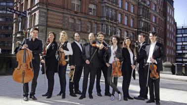 Foto der Musiker*innen der Hamburger Camerata. Mehrere Personen stehen vor einem Gebäude und halten Instrumente in der Hand. Die Männer und Frauen schauen freundlich in die Kamera und tragen schwarz/weiße Kleidung.
