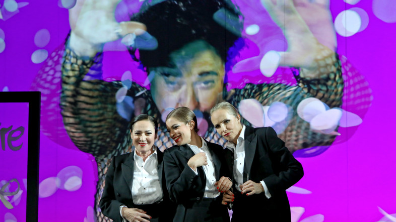 Drei Frauen stehen nebeneinander im schwarzen Anzug auf einer Bühne. Eine Frau guckt ernst, die anderen beiden lachen. Der Hintergrund ist bunt.