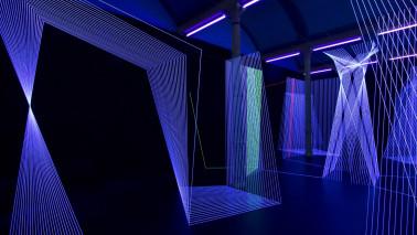 """Foto aus der Ausstellung """"Verführung Licht"""" aus dem Staatlichen Museum Schwerin. Zu sehen ist ein dunkler raum, der in den Farben Lila und Blau beleuchtet ist. Zudem sind einige Laserstrahlen zu sehen."""