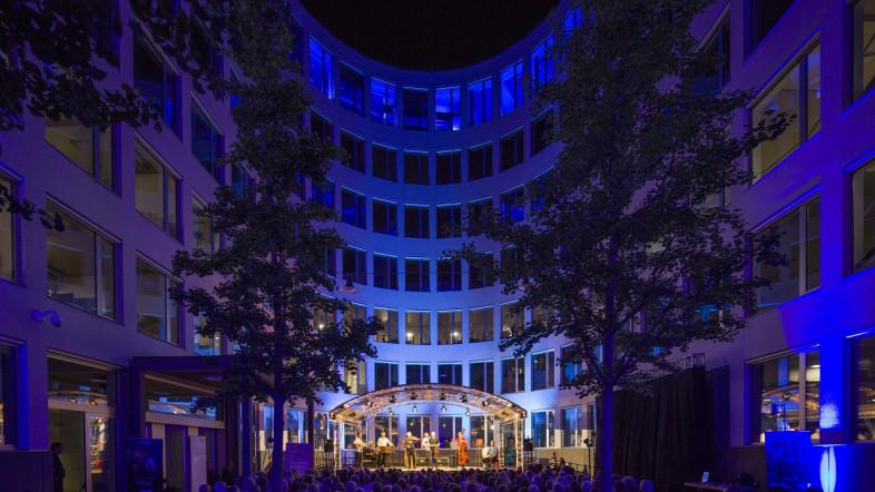 Fotografie der Eröffnung des Musikfestes Bremen. Die Bühne und die Zuschauerplätze sind in einem Innenhof aufgebaut. Das Foto wurde aus Sicht des Publikums Richtung Bühne geschossen.