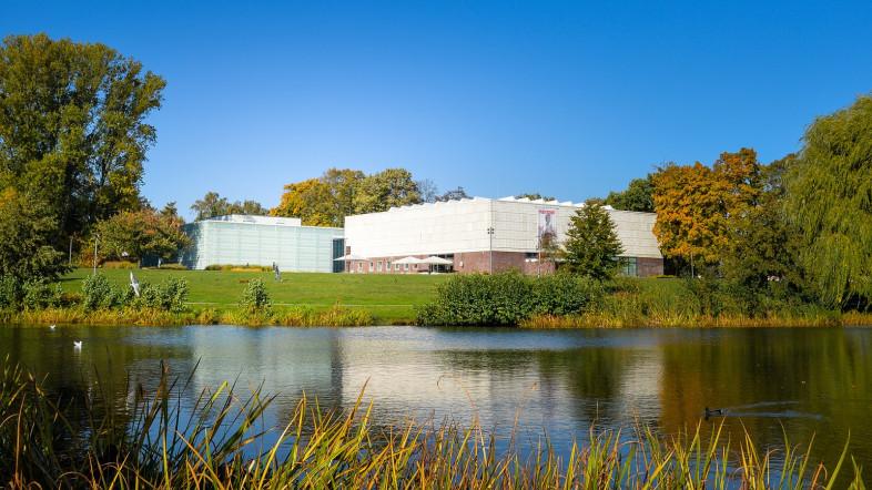 Foto der Außenansicht der Kunsthalle Rostock. Im Vordergrund ist ein See zu sehen und im Hintergrund die Kunsthalle Rostock.