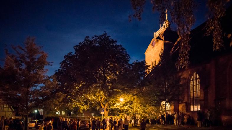 Foto bei Nacht Menschen stehen vor einer Kirche.