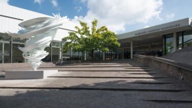Eingangsbereich des Sprengel Museums Hannover. Auf der linken Seite ist ein weißes Kunstwerk und ein Baum zu sehen. Der Himmel ist blau mit ein paar Wolken und die Sonne scheint.