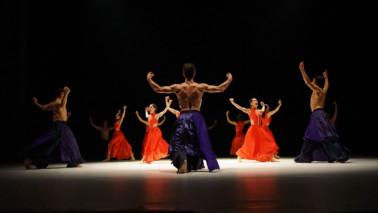 Mehrere Männer und Frauen stehen auf Bühne und strecken die Arme weit geöffnet in die List. Die Männer tragen lilane Hosen und sind oberkörperfrei. Die Frauen tragen orangene Kleider