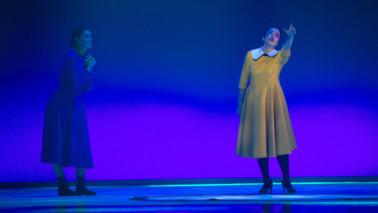 Zwei Frauen auf der Bühne. Eine Frau im gelben Kleid im Rampenlicht, die andere links im Hintergrund. Der Hintergrund wird mit blauem und lilanen Licht bestrahlt.