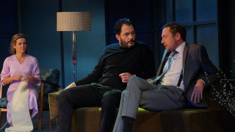 Zwei Männer sitzen auf einer Couch und unterhalten sich. Links im Hintergrund sitzt eine Frau im rosenen Kleid und strickt eine weiße Decke.