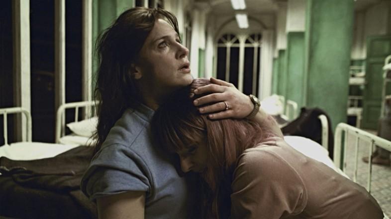 Eine Frau hält eine andere Frau in den Armen und tröstet sie.