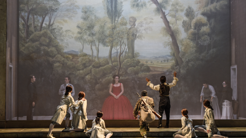 Eine Frau steht in einem roten Kleid auf einer Treppe. Um sie herum sind mehrere Männer und schauen sie an. Im Hintergrund ist ein Wald.