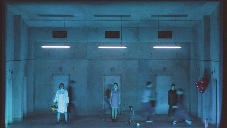 Mehrere Personen stehen mit einem weißen Kittel vor einer Betonwand.