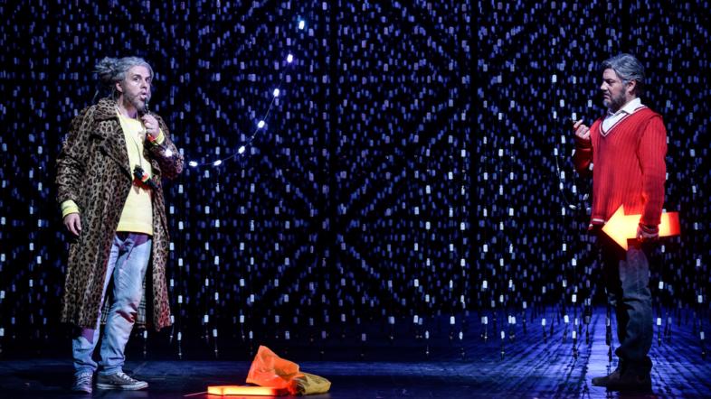 Zwei Männer stehen gegenüber auf der Bühne und sehen sich an. Einer hat eine Flöte in der Hand. Der Hintergrund ist mit Lichterketten behangen.
