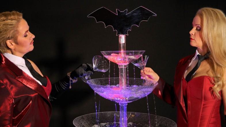 Ein Mann und eine Frau stehen vor einem Glasbrunnen und füllen zwei Gläser mit Wasser auf. Auf dem Brunnen steckt eine Fledermaus.