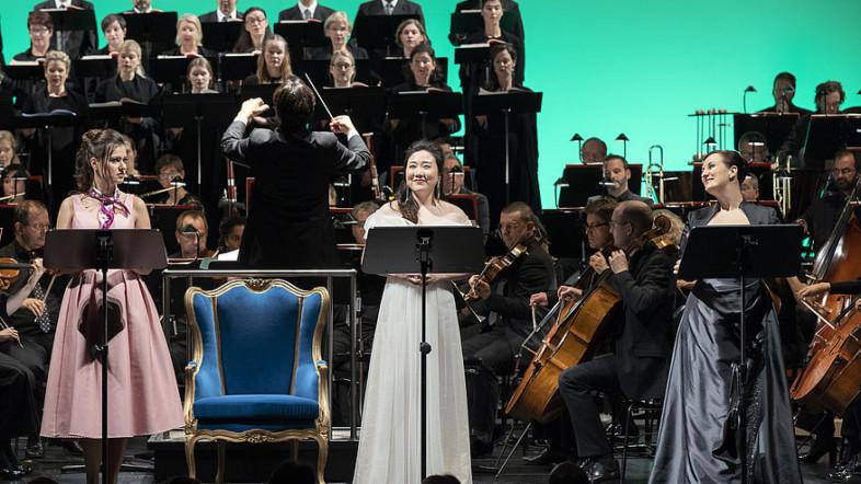 Im Vordergrund stehen zwei Frauen jeweils vor einem Podest. Im Hintergrund ist ein Orchester zu sehen.