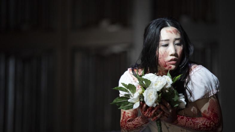 Eine asiatische Frau mit einem, blutverschmierten weißen Kleid hält weißen Blumen in ihrer Hand und wirkt verängstigt.