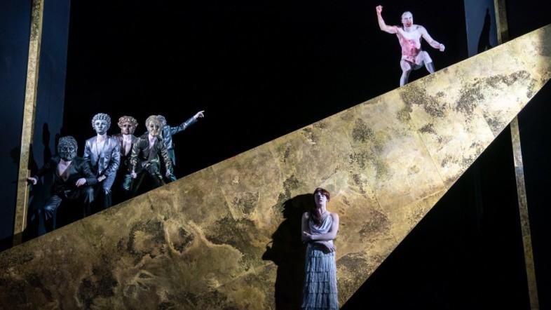 Eine Frau steht vor einer goldenen Figur. Auf der Figur stehen mehrere Personen, die eine Maske tragen und ein blutverschmierter Mann, der verärgert aussieht.