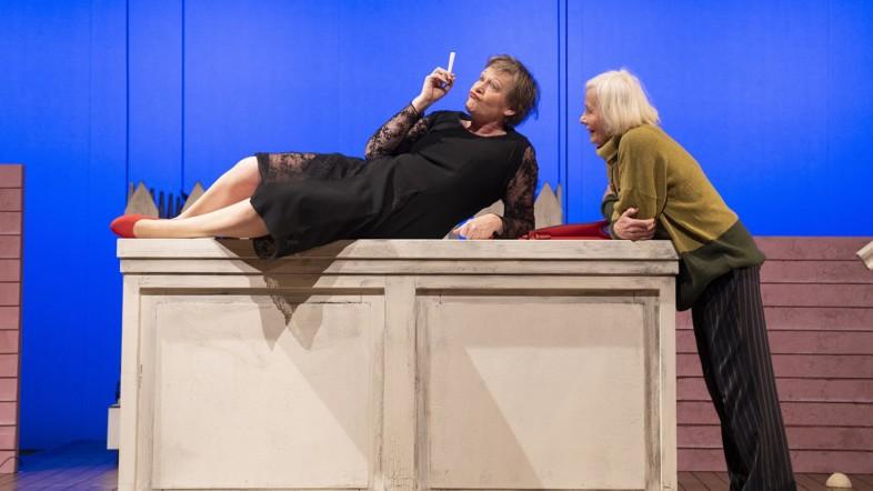 Zwei Frauen auf einer Theaterbühne mit blauem Hintergrund. Eine Frau liegt auf einer hellen Kommode und ist schwarz gekleidet. Die andere Frau trägt einen gelben Pullover und ist mit Blick zur anderen Frau an die Kommode gelehnt