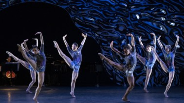 Mehrere Ballett-Tänzer auf der Bühne mit blauen Kostümen.