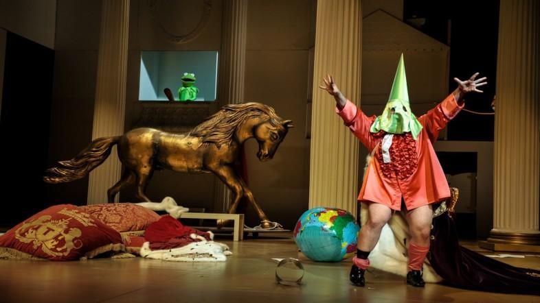 Die Kulisse ähnelt einem Kinderzimmer. Auf der rechten Seite steht ein Mann mit roter Kleidung und trägt einen grünen Hut kombiniert mit einem grünen Maske.
