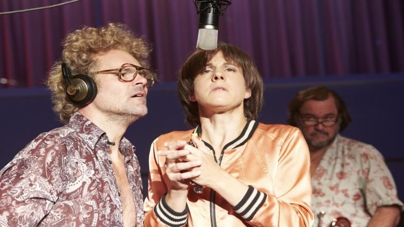 Eine Frau steht vor einem Mikrofon und faltet die Hände zusammen. Neben ihr steht ein Mann, der Kopfhörer trägt.