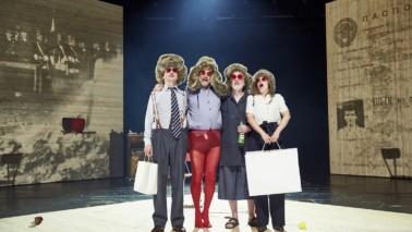 Vier Personen in einer Reihe nebeneinander und tragen Perücken. Die jeweilige Person links und rechts außen hält einen Koffern in der Hand.