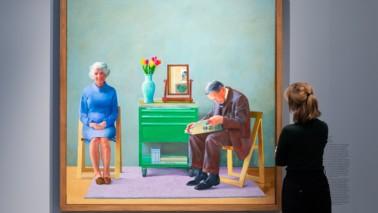 Eine Frau steht vor einem Gemälde. Auf dem Gemälde ist eine Frau und ein Mann zu sehen, die an einem Tisch sitzen. Der Mann ließt Zeitung, Das Bild ist Bund und hängt an einer schlichten Wand