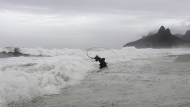 Fotografie eines Gemäldes auf dem eine Frau zu sehen ist, die am Strand im Wasser steht und eine Peitsche schwingt. Die Frau ist schwarz gekleidet.