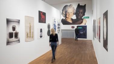 Fotografie einer Ausstellung. Plakate hängen an weißen Wänden. Eine Frau läuft den Gang herunter.