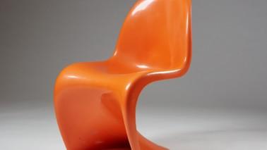 Fotografie eines Stuhls, der auf dem Boden vor einer grauen Leinwand steht. Der Stuhl ist orange.