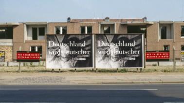 """Fotografie von zwei Plakaten, die vor einem Hausblock stehen. Das Plakat ist schwarz weiß und darauf ist """"Deutschland wird deutscher"""" nieder geschrieben."""