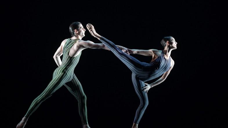 Zwei Ballett-Tänzer tanzen in Kostümen auf einer Bühne vor einem schwarzem Hintergrund.