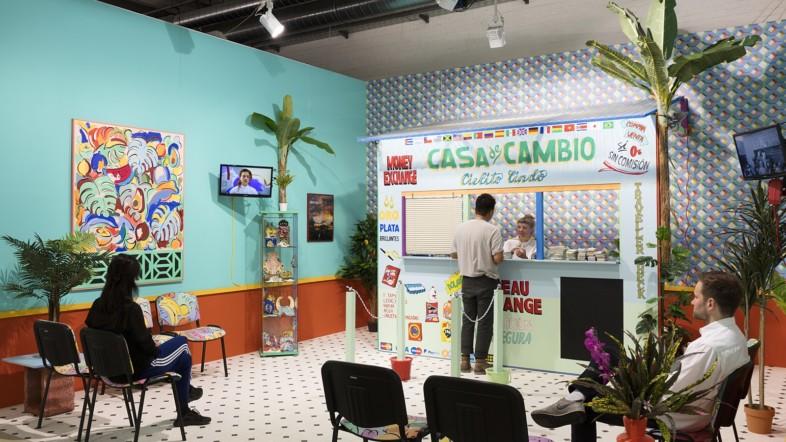 Fotografie eines Warteraums. Zwei Personen sitzen auf Stühlen, eine Person steht vorne am Tresen. Es hängen Bilder an den Wänden, mehrere Pflanzen sind zu sehen und der Raum ist sehr bunt.