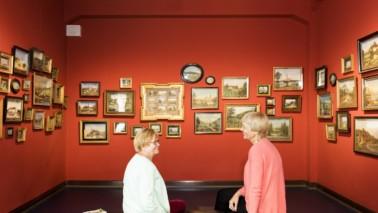 Zwei Frauen sitzen vor einer roten Wand, an der mehrere Bilder hängen. Sie schauen sich an und unterhalten sich.