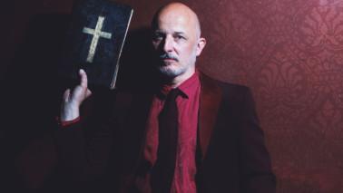Foto des Schauspielers Lukas Holzhausen. Herr Holzhausen sitzt vor einer roten Wand, trägt einen Anzug und hält in seiner rechten Hand ein Buch mit einem weißen Kreuz bedruckt.