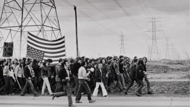 Einen schwarz-weiß Fotografie, auf der eine Gruppe von Menschen auf der Straße läuft. Im Hintergrund sind Strommaste zu sehen.