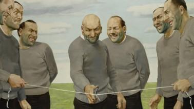Mehrer Männer, alle gekleidet in schwarzer Hose und grauem Sweatshirt, stehen auf einer Wiese. Ein Mann auf der linken und ein Mann auf der rechten Seite halten jeweils das Ende einer Schnur. Ein Mann in der Mitte hat eine Schere in der Hand und zerschneidet die Schnur.